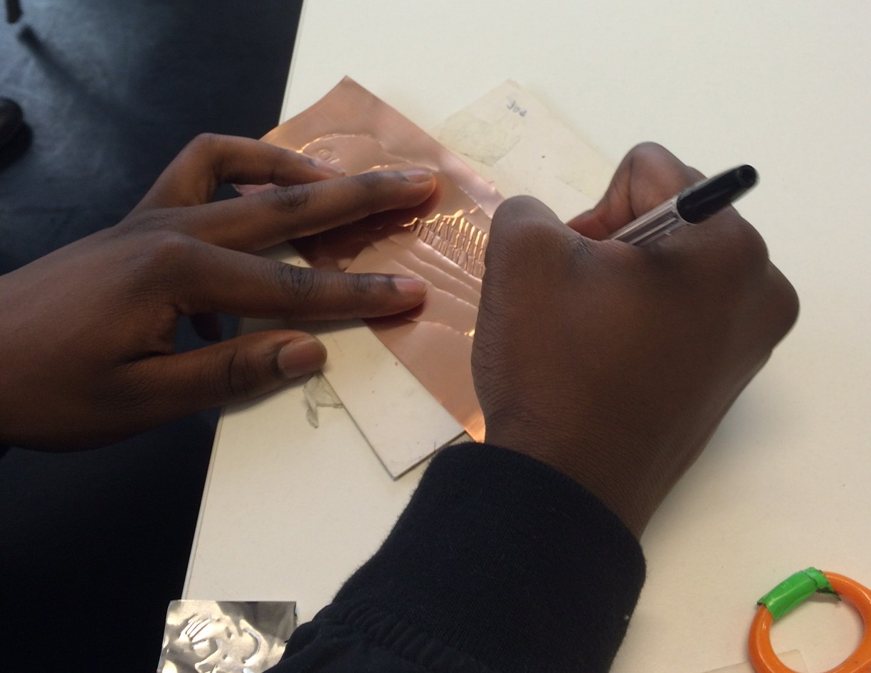 Hands drawing into copper metal to make an imprint