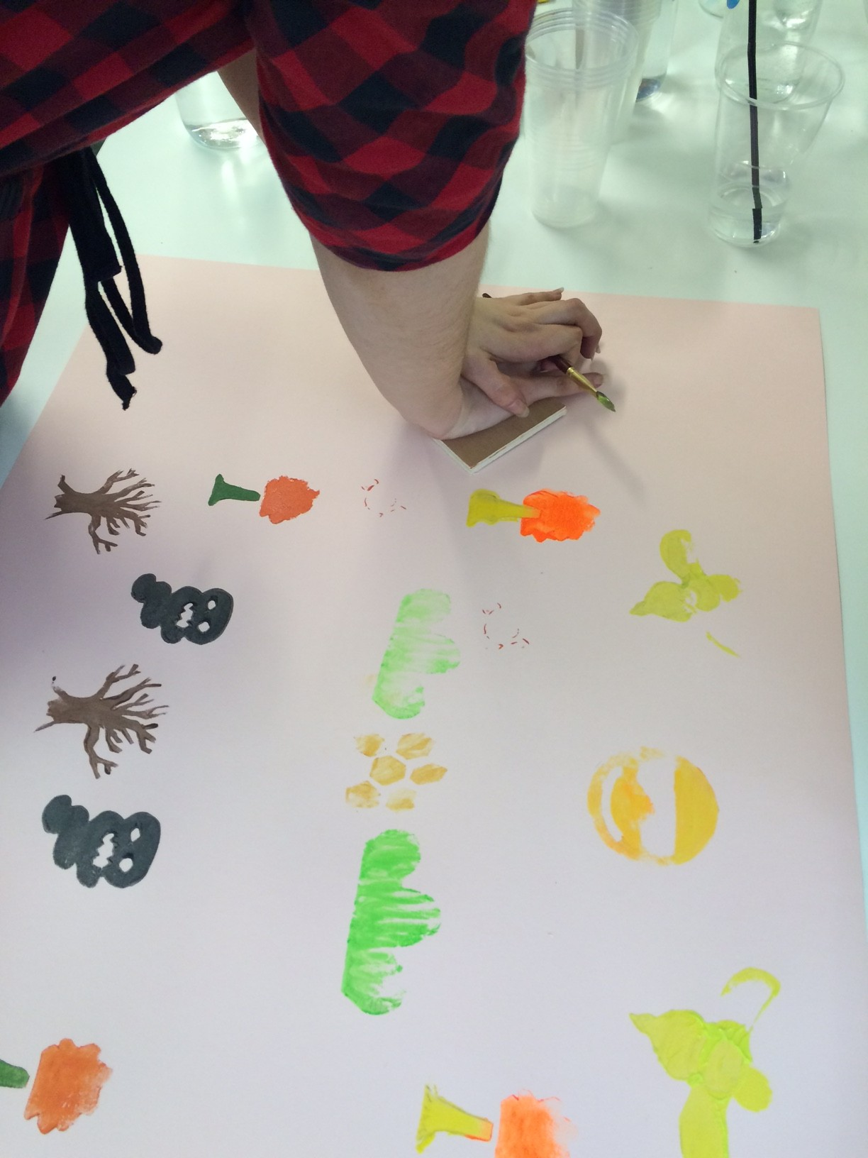 Stamping a large piece of paper with an image of a bee