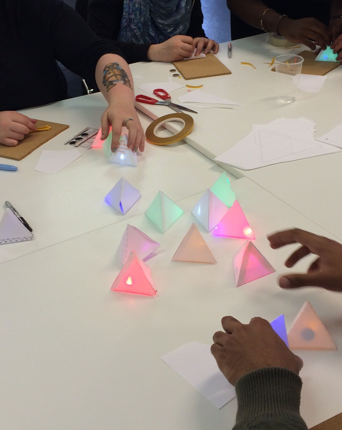 The group are placing their colourful light up paper pyramids in the centre of the table.