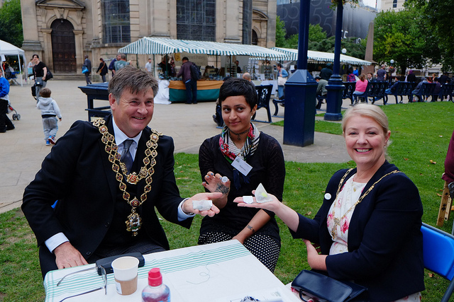 Manaz sits at an outdoor table with the Lord Mayor who shows off the teabag he's made.