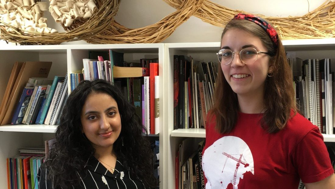 Daljinder and Hayley stand smiling in front of a bookcase