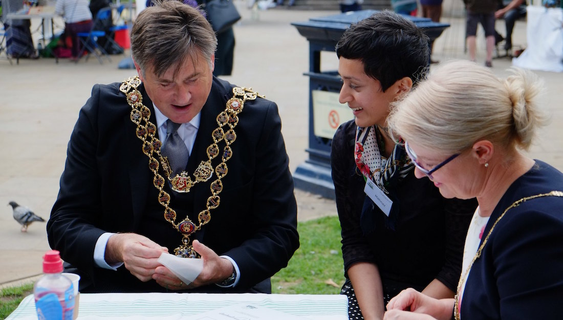 Mahnaz talks to the Mayor of Birmingham who is stitching a tea bag