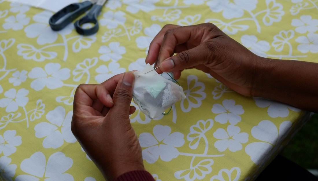 hands stitching a fabric tea bag