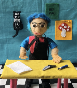 An image made out of felt, showing a woman with blue hair stood at a table with craft materials.