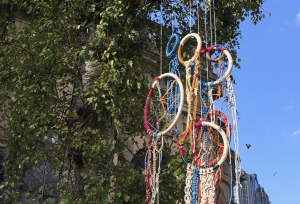 A macrame dream catcher hanging from a tree against a blue sky.